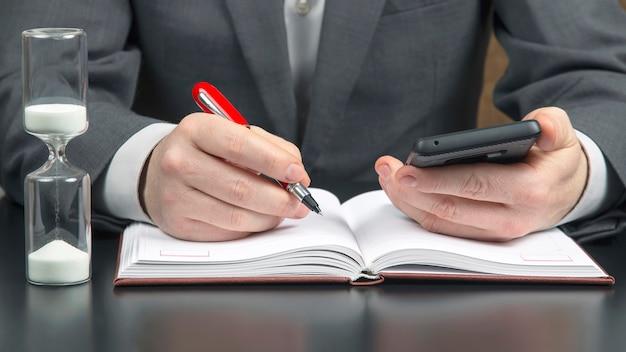 Działalności człowieka w biurze pracuje z telefonem komórkowym na tle klepsydry. biznes i udany cel