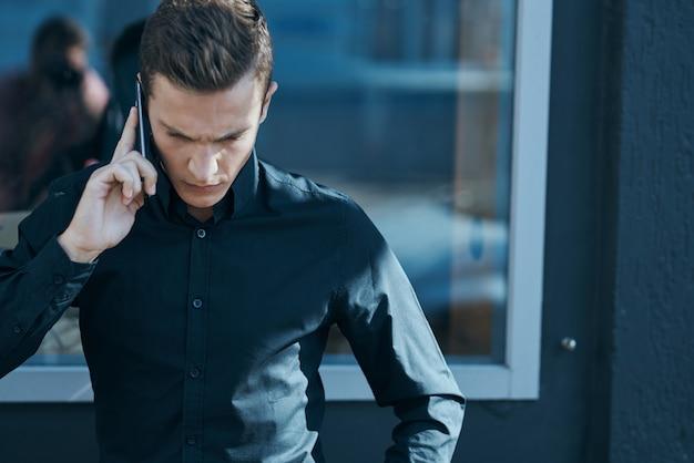 Działalności człowieka w czarnej koszuli rozmawia przez menedżera telefonu na zewnątrz.