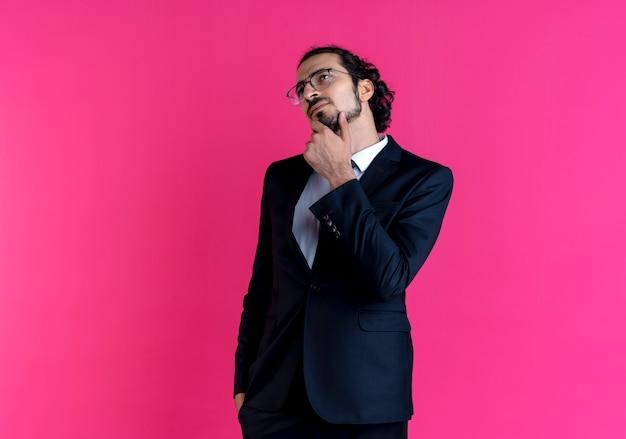 Działalności człowieka w czarnym garniturze i okularach patrząc na bok z ręką na brodzie zdziwiony stojąc nad różową ścianą