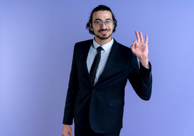 Działalności człowieka w czarnym garniturze i okularach pokazano znak ok patrząc do przodu uśmiechnięty wesoło stojąc na niebieskiej ścianie