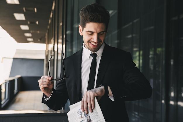 Działalności człowieka w pobliżu centrum biznesowego patrząc trzymając gazetę patrząc na zegarek.