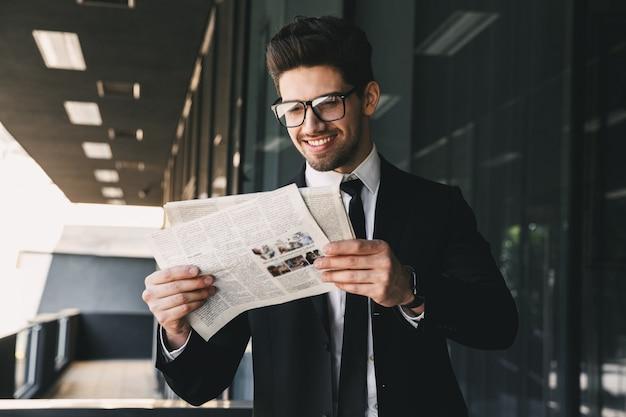 Działalności człowieka w pobliżu centrum biznesowego trzymając gazetę do czytania.