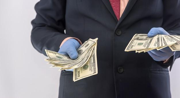 Działalności człowieka w rękawice ochronne z pieniędzmi na białym tle. koncepcja medyczna covid 19 koronawirusa