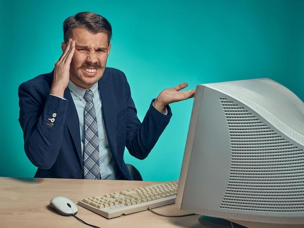 Działalności człowieka z bólem głowy, siedząc przy biurku przed komputerem