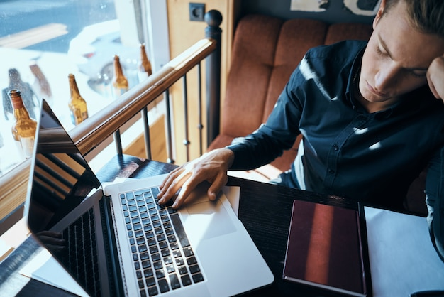 Działalności człowieka z laptopem w pracy i kawiarni modelu freelancer.