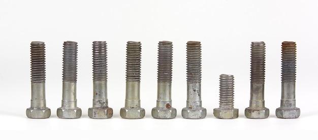 Działka koncepcyjna z dziewięcioma śrubami z nakrętkami w rzędzie. jeden obiekt jest wyjątkiem.