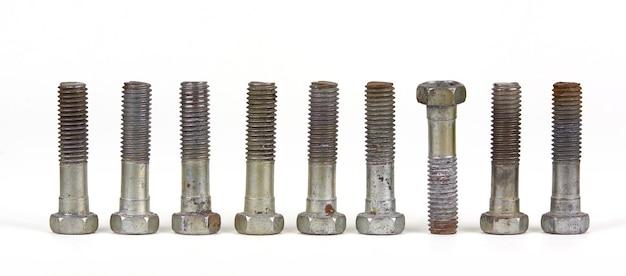 Działka koncepcyjna z dziewięcioma śrubami z nakrętkami w rzędzie. jeden przedmiot różni się od pozostałych położeniem. część jest do góry nogami.