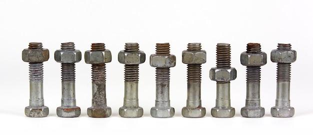 Działka koncepcyjna z dziewięcioma śrubami z nakrętkami w rzędzie. jeden przedmiot różni się od pozostałych położeniem. jedna nakrętka znajduje się poniżej pozostałych.