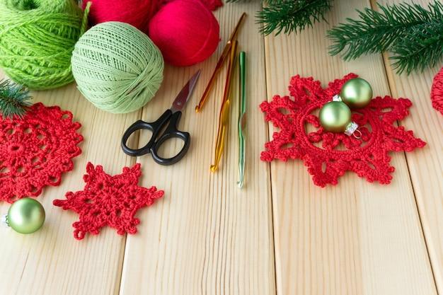 Dziane czerwone płatki śniegu, nici i haczyki na podłoże drewniane.