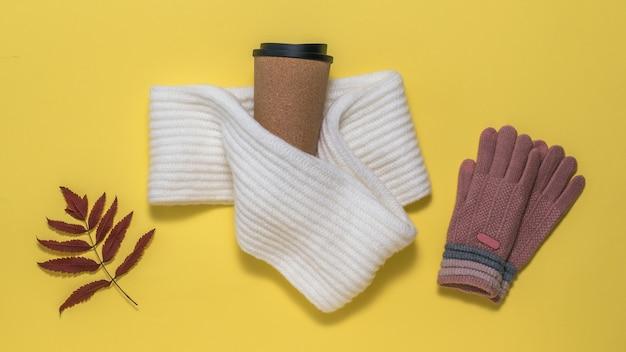Dziane rękawiczki, szalik, szklanka kawy i suszony liść jarzębiny na żółtym tle. jesienny nastrój.