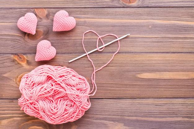 Dziane różowe serca, plątanina nici i igły na drewnianym stole.