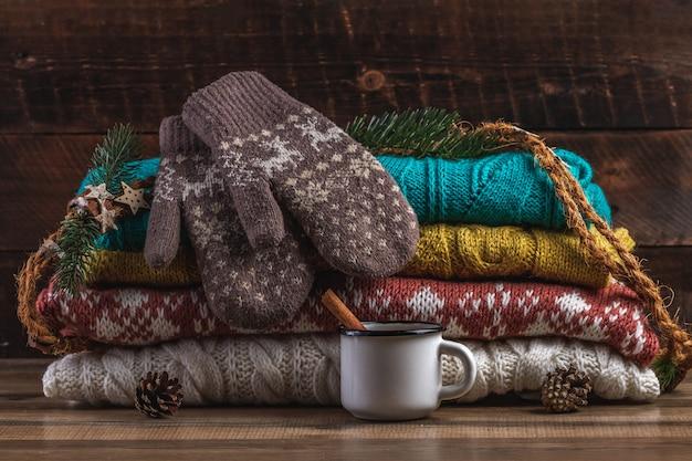 Dziane, zimowe swetry, ciepłe rękawiczki i kubek gorącego kakao. ubrania zimowe.