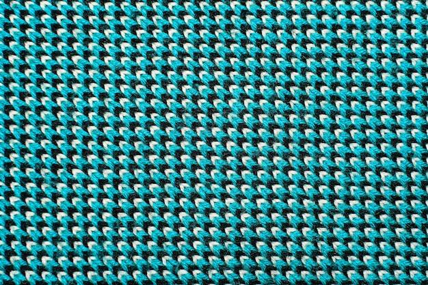 Dzianina syntetyczna z elementami wzorzystymi z niebieskiej, czarnej i białej przędzy z bliska. wielokolorowa wzorzysta dzianina tekstura. tło