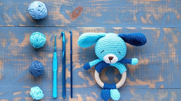 Dzianinowa niebieska zabawka dla dzieci ze sprzętem dziewiarskim na stole