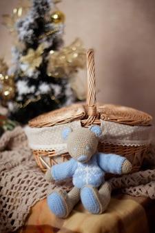Dzianinowa zabawka miś lub mysz siedzi w pobliżu wiklinowego kosza