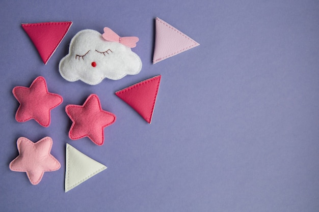 Dzianinowe zabawki w kolorach chmurki, gwiazdy, niedźwiedzia, barana, sowy, różowego i niebieskiego ptaka leżą na fioletowym tle