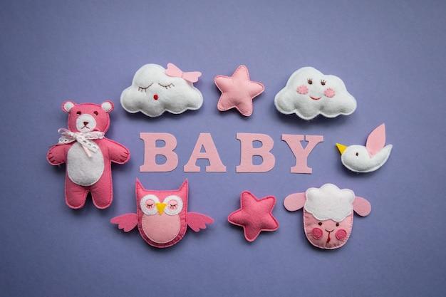Dzianinowe zabawki w kolorach chmurki, gwiazdy, niedźwiedzia, barana, sowy, różowego i niebieskiego ptaka