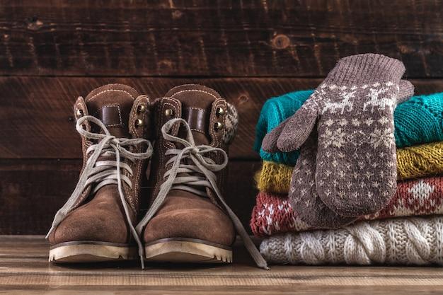 Dzianinowe, zimowe, złożone swetry, ciepłe rękawiczki i zimowe buty na drewnianym tle. ubrania zimowe. ciepłe, wygodne ubrania