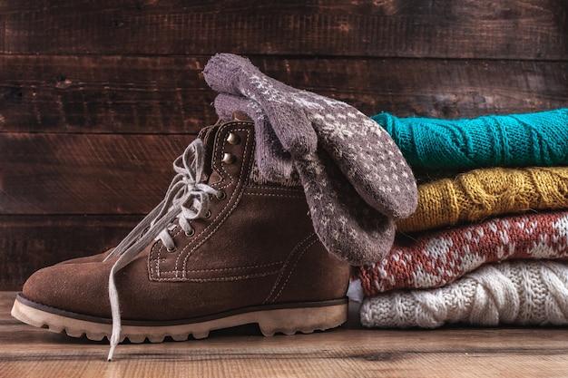 Dzianinowe, zimowe, złożone swetry, ciepłe rękawiczki i zimowe buty. ubrania zimowe. brzydki świąteczny sweter. ciepłe, wygodne ubrania