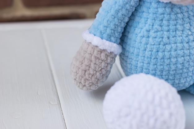 Dzianinowy miś w niebieskiej piżamie na białym tle