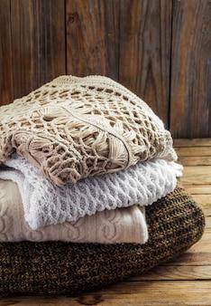 Dzianinowy przytulny sweter leżący na drewnianej ścianie