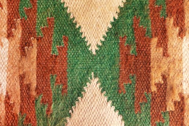 Dzianinowy wzór ornamentu etnicznego. szczegóły wnętrza dywanu tekstylnego abstrakcyjnego rzemiosła. zakończenie tekstura dywan