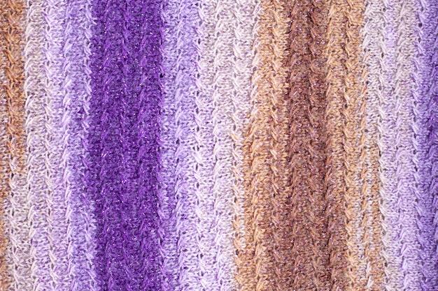 Dzianinowy wzór w kolorze fioletowo-różowo-brązowym beżowym.