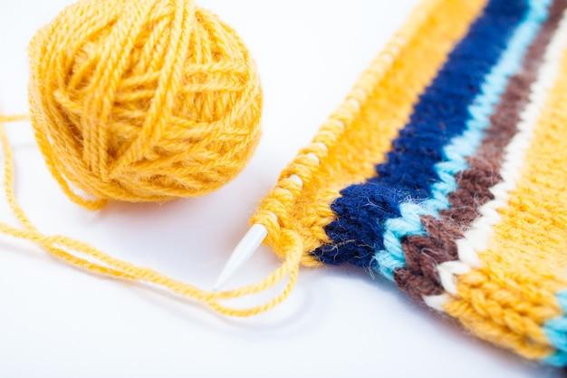 Dzianiny płótno, igła do robienia na drutach i żółta kulka z przędzy