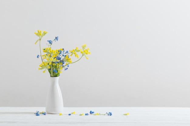 Dzicy kwiaty w wazie na bielu stole