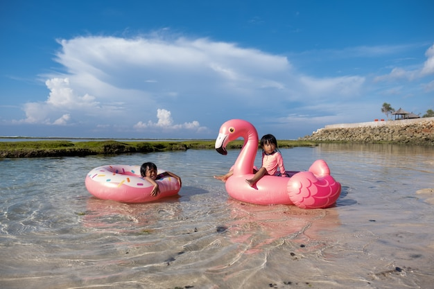 Dzieci azjatyckie cieszą się jazdą na boi ringowej i boi flamingowej