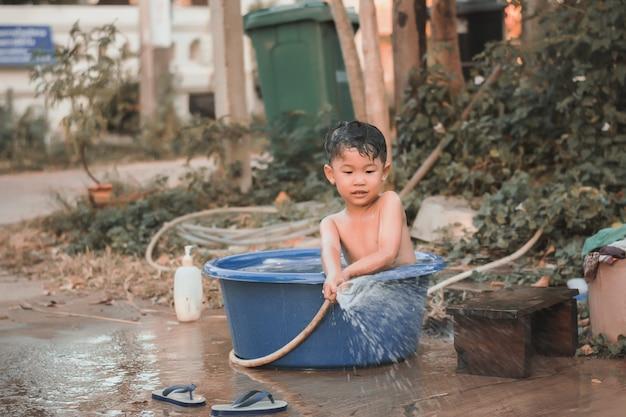 Dzieci bawią się i kąpią wodę w ogrodzie, siedząc w wiadrze z wodą.