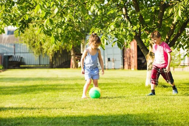 Dzieci bawią się kolorową piłką na wiejskim podwórku