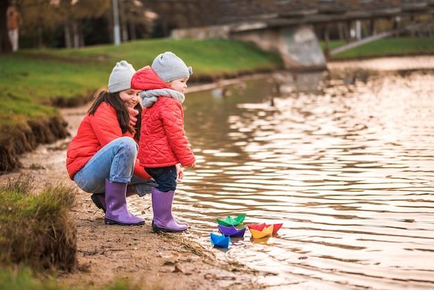 Dzieci bawią się łódkami na brzegu rzeki. słoneczna jesień. żółty park. niebieska rzeka o zachodzie słońca