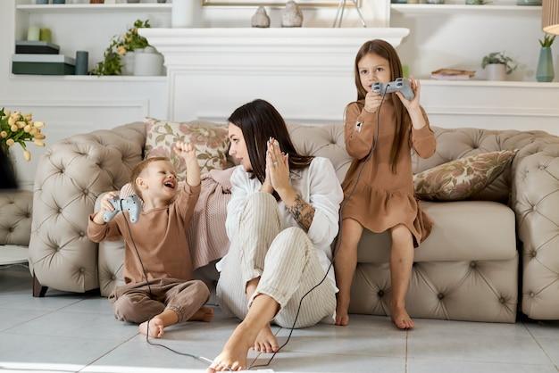 Dzieci bawią się na konsoli z mamą