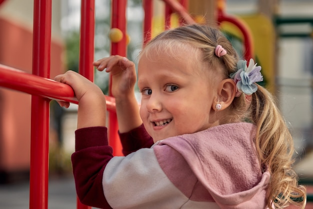 Dzieci bawią się na placu zabaw. szczęśliwa dziewczyna roześmiana baw się huśtawka i wspinaczka. aktywność na świeżym powietrzu