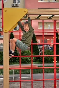 Dzieci bawią się na placu zabaw. szczęśliwy roześmiany chłopak baw się huśtawka i wspinaczka. aktywność na świeżym powietrzu