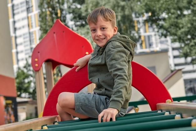 Dzieci bawią się na placu zabaw. szczęśliwy roześmiany chłopiec i dziewczynka bawią się huśtając i wspinając się. aktywność na świeżym powietrzu