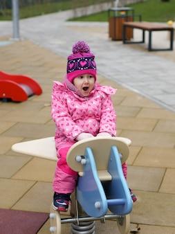 Dzieci bawią się na placu zabaw szczęśliwy roześmiany chłopiec i dziewczynka bawią się huśtając i wspinając się na świeżym powietrzu