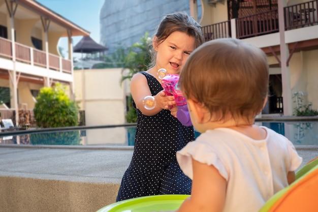 Dzieci bawią się na podwórku bańkami mydlanymi