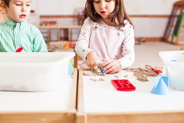 Dzieci bawią się piaskiem kinetycznym w przedszkolu