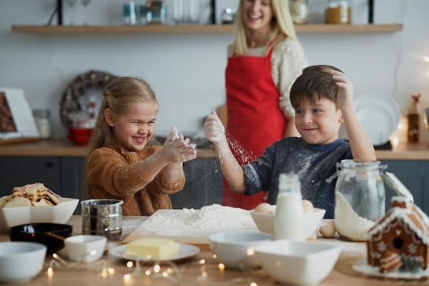 Dzieci bawią się podczas przygotowywania ciasta na świąteczne ciasteczka