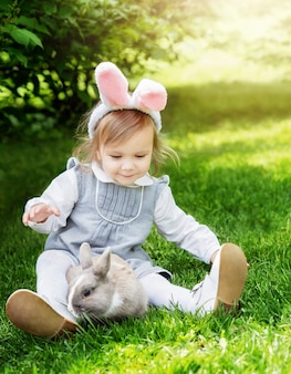 Dzieci bawią się prawdziwym królikiem. śmiejące się dziecko podczas polowania na pisanki z króliczkiem.