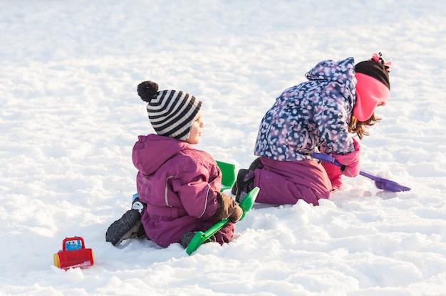 Dzieci bawią się samochodami i łopatami. koncepcja odśnieżania miasta