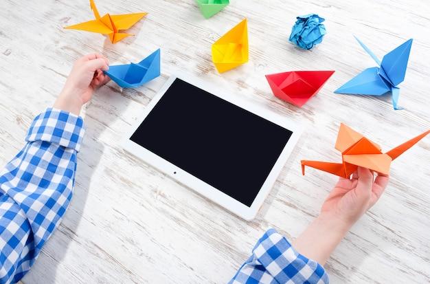 Dzieci bawią się tabletem i origami.