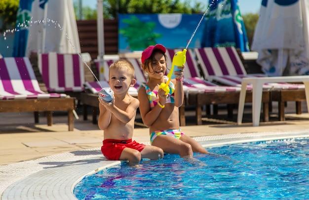 Dzieci bawią się w basenie pistoletami na wodę. selektywne skupienie. woda.