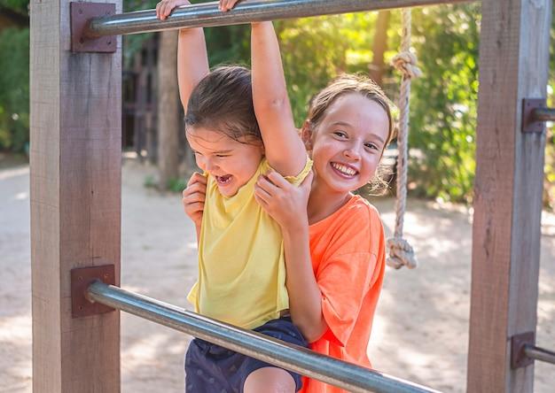 Dzieci bawią się w playgraund. starsza dziewczyna pomaga młodszej wspinać się po schodach. chroni małą siostrę
