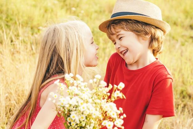 Dzieci bawią się w polu na tle przyrody. cicha sympatia. słodkie dzieci anioła. walentynki