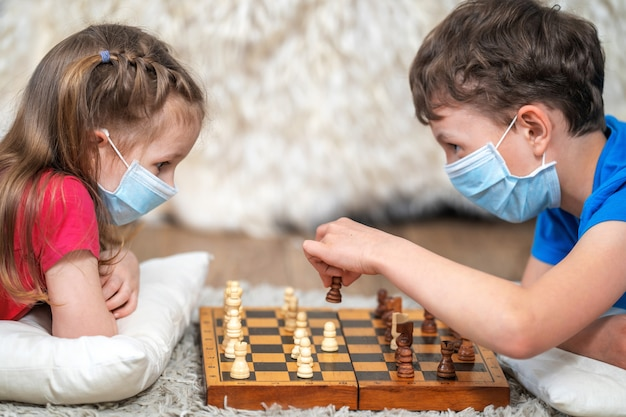 Dzieci bawią się w szachy w medycznych maskach na twarzy, leżą na podłodze. zostań w domu