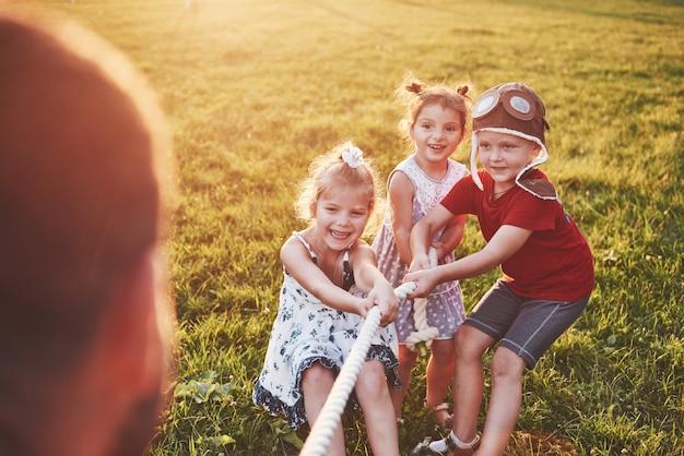 Dzieci bawią się z tatą w parku. ciągną linę i bawią się w słoneczny dzień