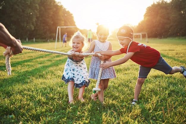 Dzieci bawią się z tatą w parku. ciągną za linę i bawią się leżąc w słoneczny dzień
